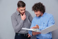 Portrait of a two casual businessmen reading documents in folder over gray background