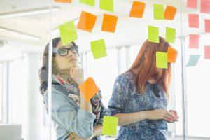 Women studying ideas written on a wall