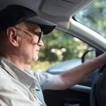Side view of an elderly man in glasses driving a car on a sunny summer day