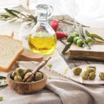 Lunch with green olives, bread and olive oil served with vintage book on old wooden table near window. See series
